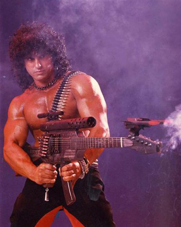 Rambo parody, 1980s dude, big hair, with machine gun guitar